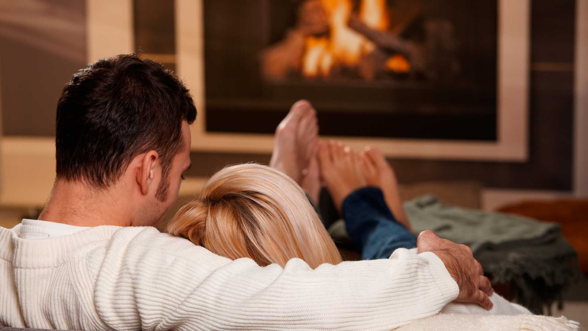 image shows man and woman sat infront of their gas fire